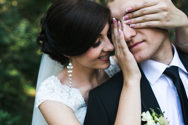 smiling-bride-playing-with-her-husband_1153-627