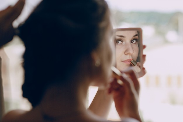 bride-making-up-in-a-small-mirror_1157-808