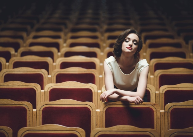 woman-sitting-in-the-armchairs-of-a-theater_1304-532