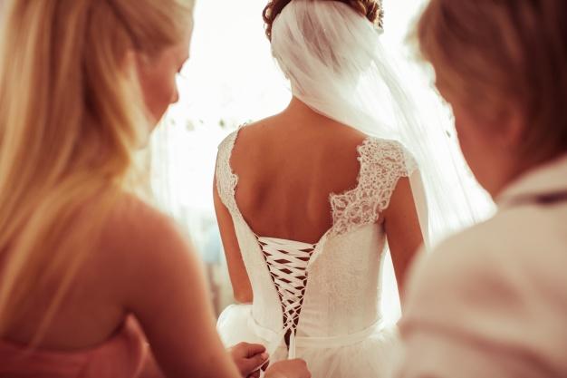 bridesmaid-climbing-the-zipper-of-a-wedding-dress_1304-407