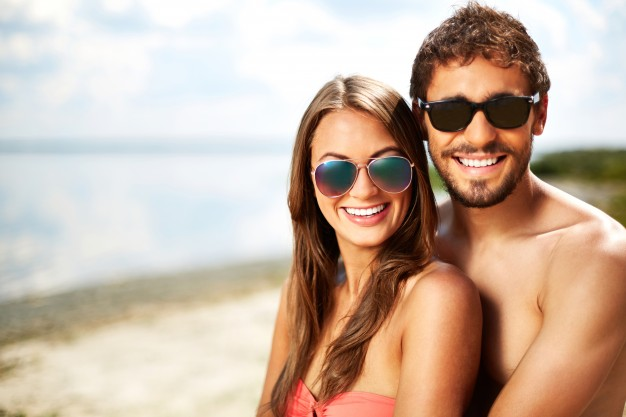 couple-with-sunglasses-on-the-beach_1098-2484