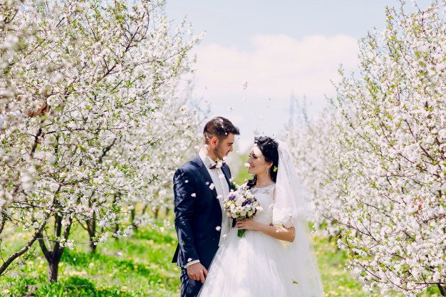 newlyweds-looking-at-each-other-with-flowers-falling-from-the-sky_1157-399