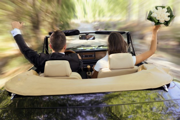 bride-and-groom-driving-the-wedding-car_1139-447