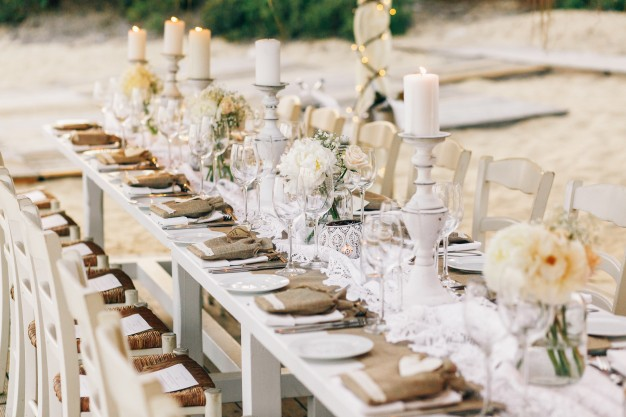 long-dinner-table-decorated-with-flaxen-cloth-and-white-candles_1304-3245