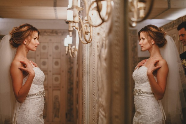 woman-lookin-his-wedding-dress-in-the-mirror_1157-188
